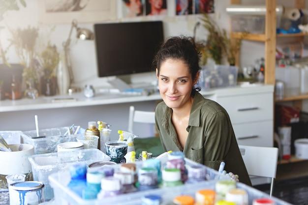 Prise De Vue à L'intérieur D'une Femme Peintre Créative Avec Une Belle Apparence Assise à Table Entourée D'huiles Colorées Photo gratuit