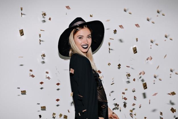 Prise De Vue En Studio à L'intérieur D'un Incroyable Modèle Féminin En Tenue Noire Souriant Photo gratuit