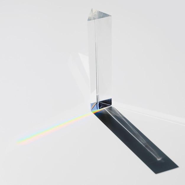 Un prisme dispersant la lumière du soleil se divisant en un spectre sur fond blanc Photo gratuit