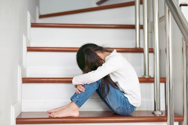Problème enfant contrarié avec tête dans les mains, assis sur le concept de l'escalier Photo Premium