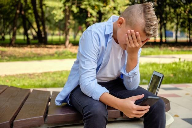 Problèmes des enfants modernes. jeune mec dans le parc avec le téléphone contrarié Photo Premium