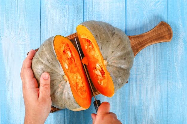 Procédé de coupe de morceaux de citrouille pour la cuisson de soupe ou de purée de citrouille citrouille sur une table en bois bleue Photo Premium