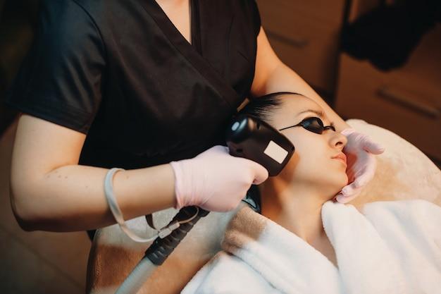 Procédure D'épilation Du Visage Faite à Une Femme Brune à L'aide D'appareils Modernes Au Salon Spa Photo Premium