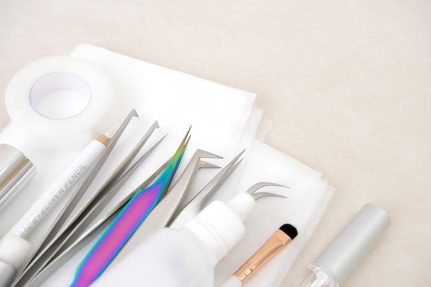Procédure d'extension de cils. outils. colle, pincettes, pinceaux. salon de beauté, mode et femme composent le concept Photo Premium