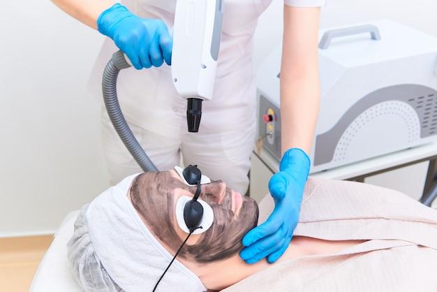 Procédure de gommage facial au carbone dans la clinique de cosmétologie laser. Photo Premium