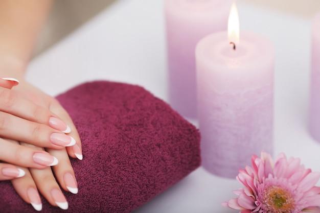 Procédure de spa, femme dans un salon de beauté tenant les doigts dans un bain aromatique pour les mains Photo Premium
