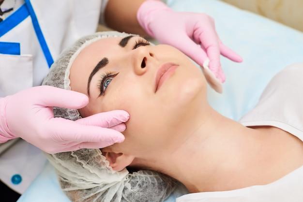 Le processus d'application d'une crème sur le visage d'une belle fille Photo Premium