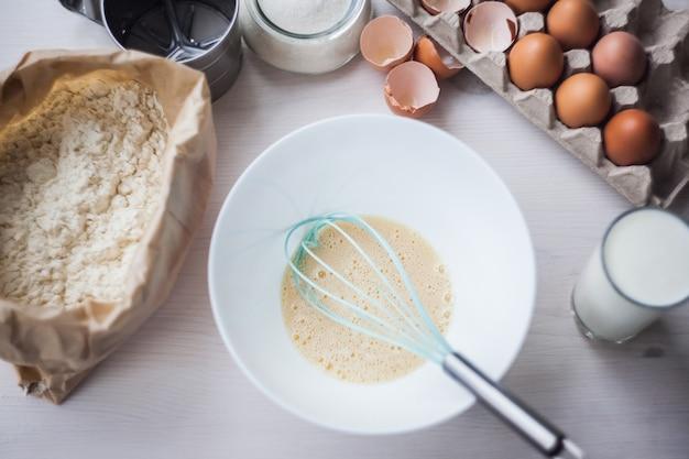 Processus de fabrication de la pâte, la main de la femme fouette les œufs et la farine dans un bol Photo Premium
