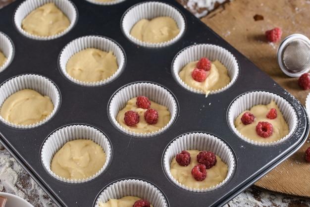 Le Processus De Fabrication De Petits Gâteaux, Enrobant Une Crème D'un Sac à Pâtisserie Entre Les Mains D'un Pâtissier. Photo Premium