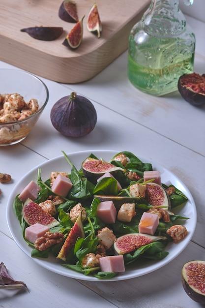 Le Processus De Fabrication De Salade Aux Figues. Salade Prête Et Ingrédients Sur Une Table En Bois Blanc. Photo Premium