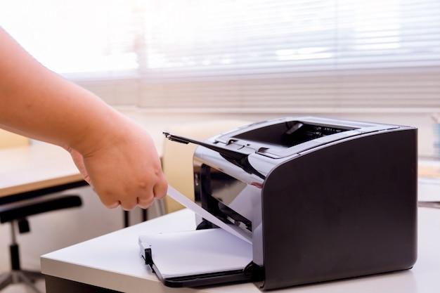 Processus de femme bussiness de la presse de papier dans l'imprimante laser. Photo Premium