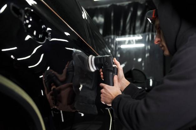 Processus De Polissage Automatique. Travailleur De Détail Polit La Carrosserie Photo Premium