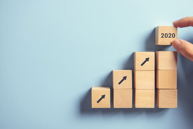 Processus de succès de croissance concept 2020 business concept, close up main femme organisant empilement de blocs de bois comme marche d'escalier sur fond de papier bleu, espace de copie. Photo Premium