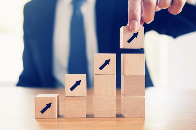 Processus De Succès De Croissance Concept Commercial, Close Up Main D'homme D'affaires Organisant Un Cube En Bois Avec Empilement De Flèche Comme Marche D'escalier. Photo Premium
