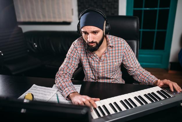 Le Producteur Sonore Au Casque Travaille Avec Un Clavier Musical En Studio. Technologie D'enregistrement Audio Numérique Professionnelle Photo Premium
