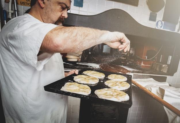 Production de pain cuit au four à bois dans une boulangerie. Photo Premium