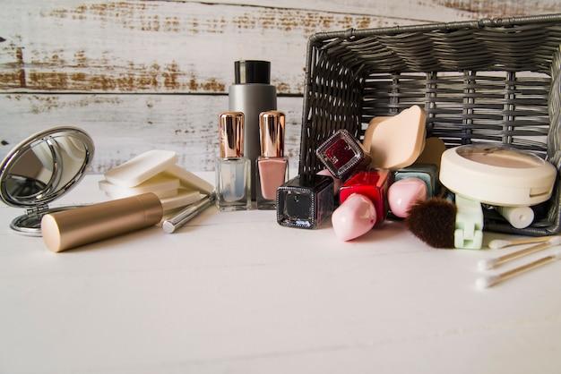 Produit de beauté cosmétique déversé du panier en osier sur la table Photo gratuit