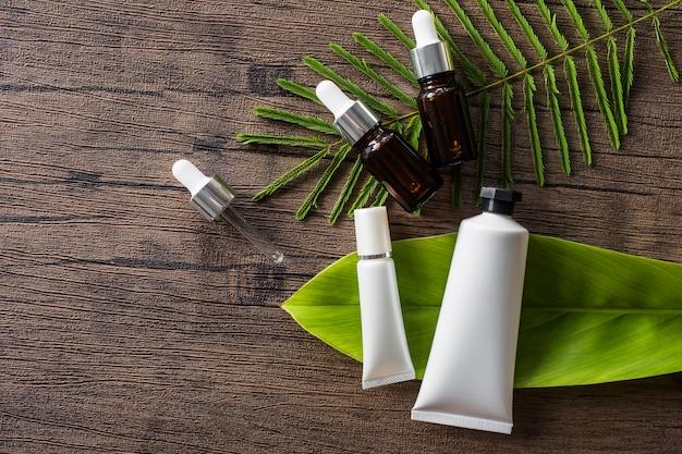 Produit cosmétique et bouteille d'huile essentielle sur des feuilles sur une table en bois Photo gratuit