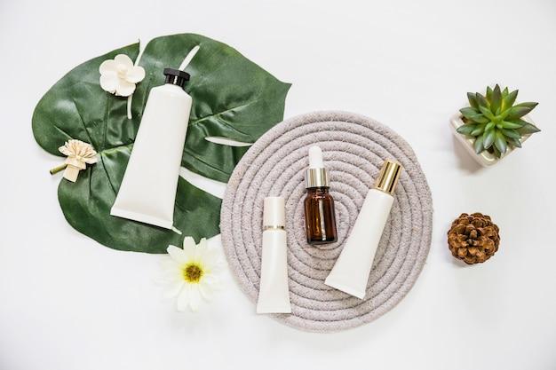 Produit cosmétique de spa sur des montagnes russes avec des fleurs; feuille; plante de pomme de pin et de cactus sur fond blanc Photo gratuit
