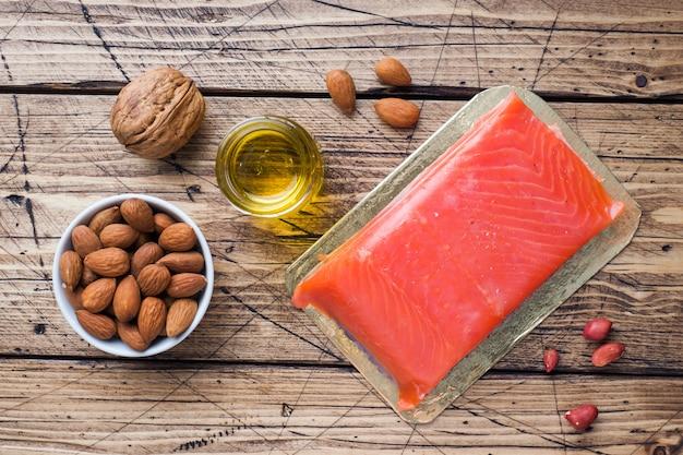 Produits antioxydants d'aliments sains: noix de poisson et huile sur fond en bois. Photo Premium