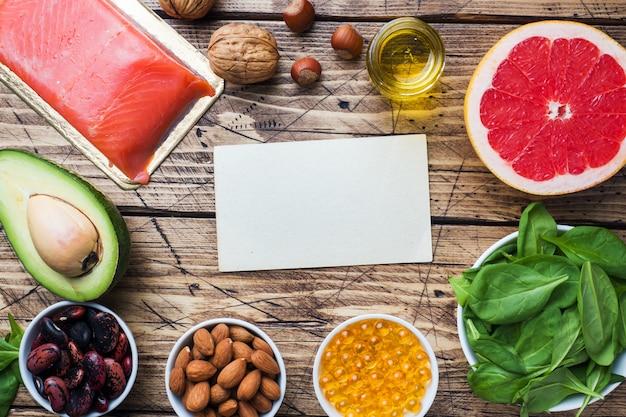 Produits antioxydants d'aliments sains: poisson et avocat, noix et huile de poisson, pamplemousse sur fond en bois. espace de copie Photo Premium