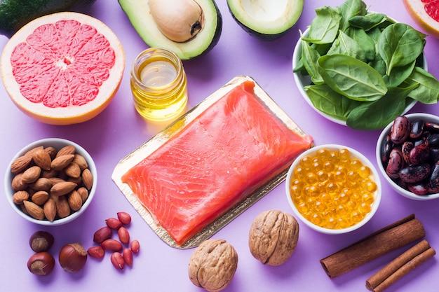 Produits antioxydants pour aliments sains: poisson et avocat, noix et huile de poisson, pamplemousse sur fond rose. Photo Premium