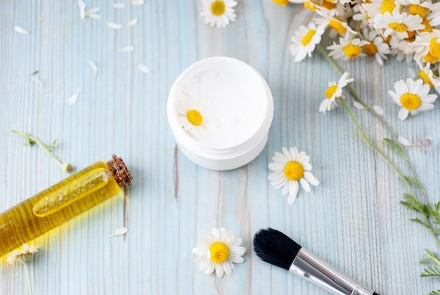 Produits cosmétiques à base de plantes faits maison avec camomille, huiles essentielles, crème pour le visage Photo Premium
