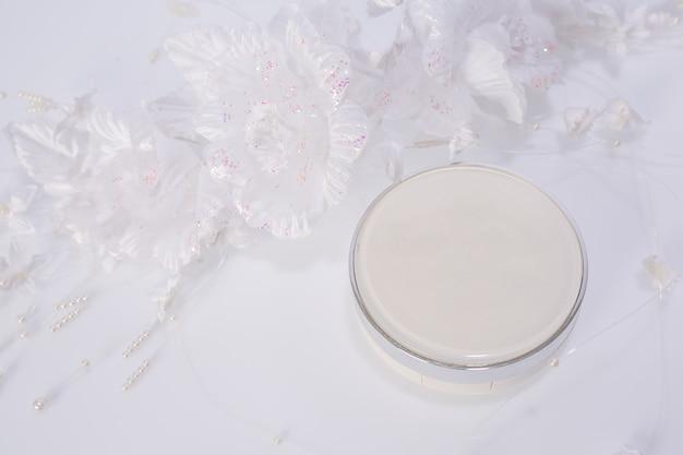 Produits cosmétiques et fleurs sur blanc Photo gratuit