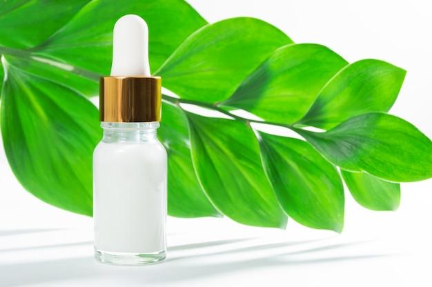 Produits cosmétiques naturels: sérum avec compte-gouttes et feuilles vertes sur fond blanc. Photo Premium