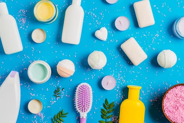 Produits cosmétiques et répandre du sel de l'himalaya sur fond bleu Photo gratuit