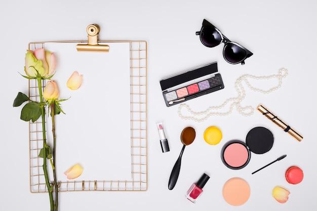 Produits cosmétiques; rose sur du papier blanc sur le presse-papiers isolé sur fond blanc Photo gratuit