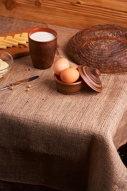 Produits laitiers biologiques lait, fromage, et aussi oeufs, pain. sur la table Photo Premium