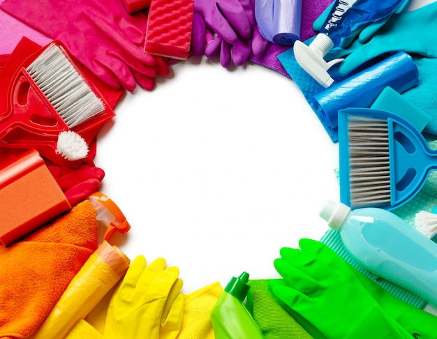 Produits de nettoyage et outils de différentes couleurs sur fond blanc. vue de dessus. encerclez la surface au milieu. Photo Premium