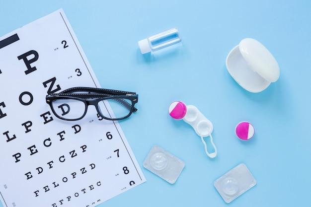 Produits de soins oculaires plats sur fond bleu Photo gratuit