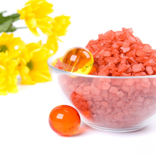 Produits de spa: sel de bain, boules d'huile dans un bol et fleurs jaunes Photo Premium
