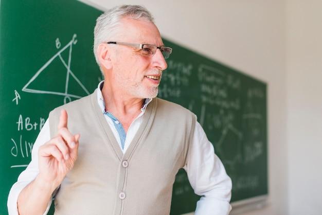 Professeur âgé, donnant des conférences près d'un tableau dans une salle de classe Photo gratuit