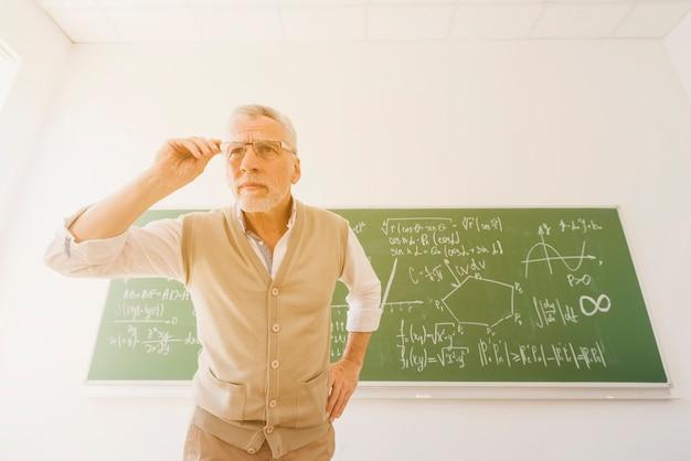 Professeur âgé regardant à travers des lunettes dans la salle de classe Photo gratuit