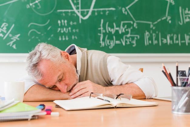 Professeur aux cheveux gris dormant sur la table Photo gratuit