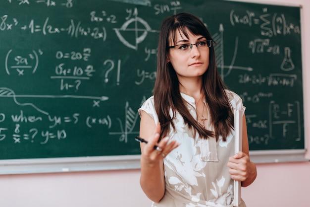 Le professeur debout à côté d'un tableau et explique une leçon. Photo Premium