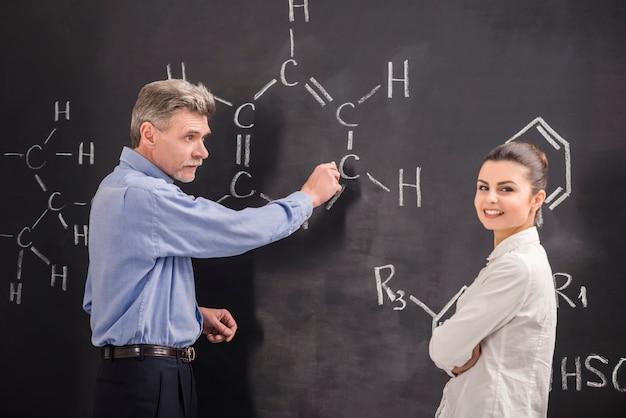 Professeur et femme écrivent ensemble sur une formule de tableau noir. Photo Premium