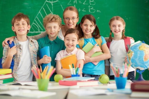 Professeur fier avec ses élèves du primaire Photo gratuit