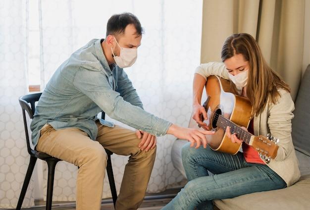 Professeur De Guitare Montrant à La Femme Comment Jouer Photo gratuit