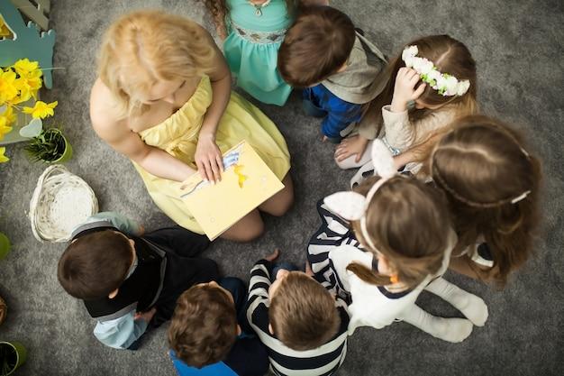 Le professeur lit un livre aux enfants Photo Premium