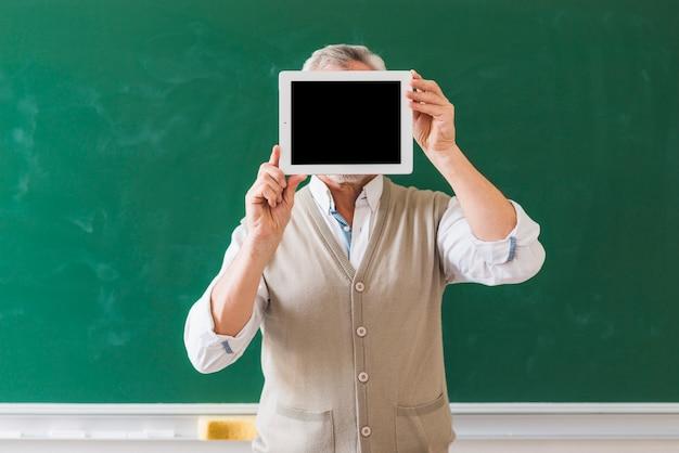 Professeur Montrant Un Espace Vide Sur Une Tablette Dans La Salle De Classe Photo gratuit