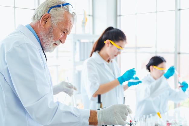 Professeur de sciences et équipe d'étudiants travaillant avec des produits chimiques en laboratoire Photo Premium
