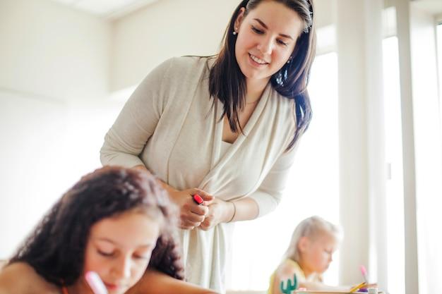Professeur de sexe féminin se penchant sur une écolière Photo gratuit