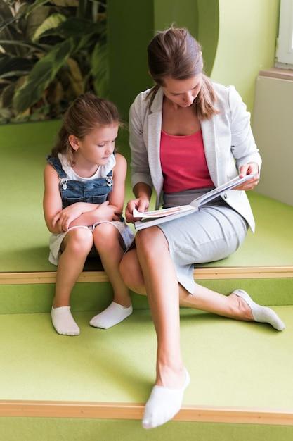 Professeur De Tir Complet Et Fille Avec Livre Photo gratuit