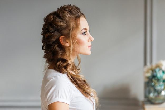 Le profil de la belle jeune fille sur fond de mur gris. Photo gratuit