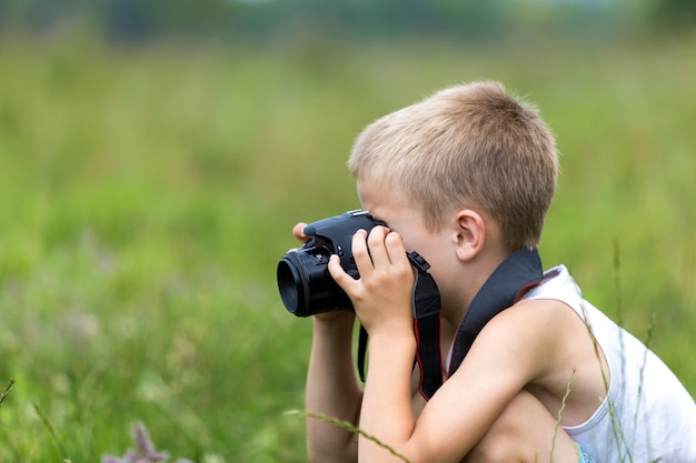 Profil portrait en gros plan du jeune garçon d'enfant beau et blond avec l'appareil photo prenant des photos à l'extérieur sur le printemps ensoleillé lumineux. Photo Premium