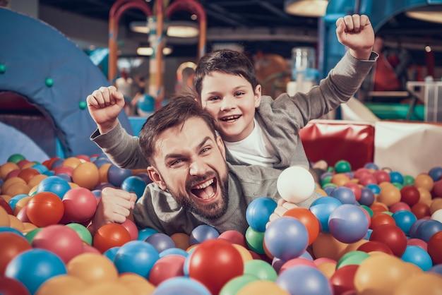 Profiter Du Père Et Du Fils Dans La Piscine Avec Des Balles Au Centre. Photo Premium